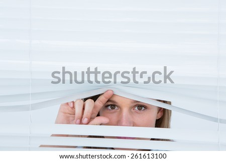 Woman peering through roller blind on white background - stock photo