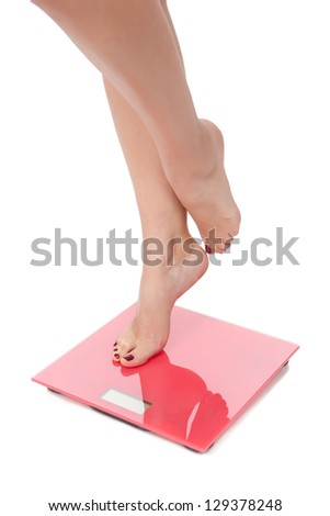 Woman perfect shaped legs on scale on white background - stock photo