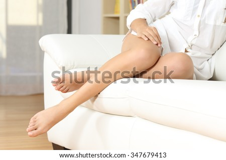 Woman perfect waxed legs resting on a couch at home