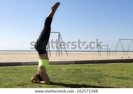 Woman performing a balancing headstand - stock photo