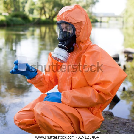 Woman performing water sampling and analysis in protective suit