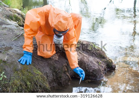 Woman performing water sampling and analysis outside - stock photo