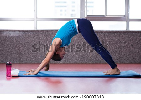Woman performing yoga pose in the gym - stock photo