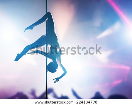 Woman performs sensual, passionate pole dance in night club. Sexy body silhouette, professional, sexual pose. - stock photo