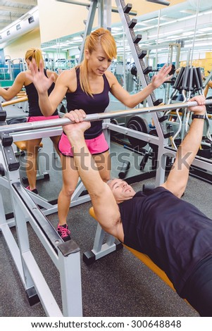 Woman personal trainer encouraging to muscle man in a bench press training with barbell on fitness center. Motivation in training concept.