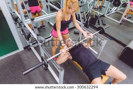 Woman personal trainer helping to muscle man for a correct bench press training with barbell on fitness center - stock photo