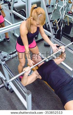 Woman personal trainer helping to muscle man for a correct bench press training with barbell on fitness center