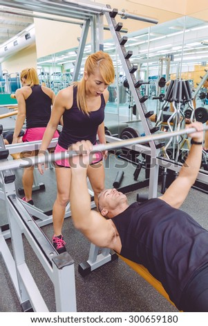 Woman personal trainer screaming to muscle man in a bench press training with barbell on fitness center. Motivation in training concept. - stock photo