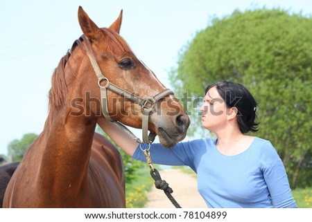 Woman petting brown horse