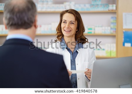 Woman pharmacist helping a male customer dispensing his prescription medicine with a friendly smile