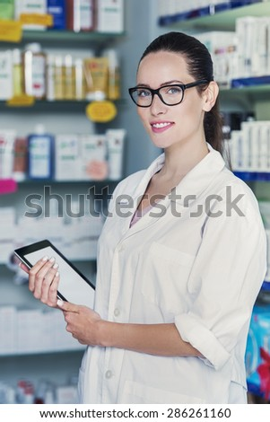 woman pharmacist is holding a tablet pc - stock photo