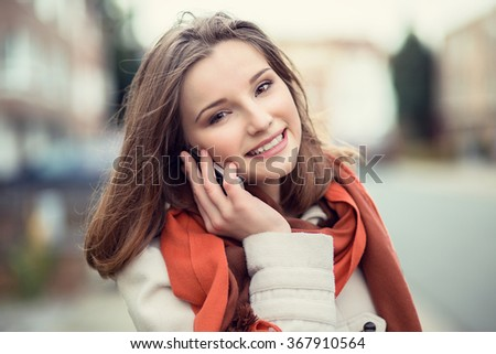 Woman phone talking. Closeup young happy beautiful smiling woman girl lady talking on mobile cell phone isolated cityscape outdoor street background. Positive face expression human emotion attitude - stock photo