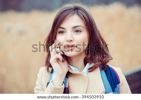 Woman phone talking. Closeup young happy beautiful woman girl lady talking on mobile cellphone looking up thinking isolated park cityscape outdoor background. Positive face expression human emotion - stock photo