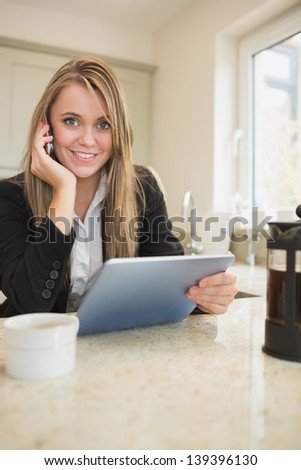 Woman phoning and holding a tablet in kitchen
