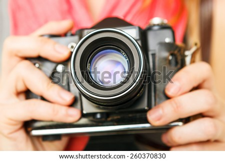 Woman photographer holding old 35mm film camera. - stock photo