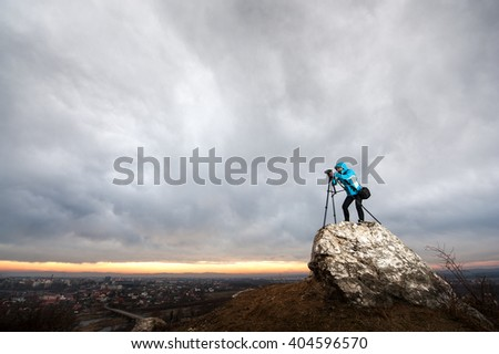 Woman photographer is standing with her camera on tripod on the big rock at city overview point. Female is taking picture of the nature - stock photo