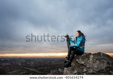 Woman photographer sitting on the big rock at city overview point at the sunset in the mountains with her camera on tripod. Dark blue clouds on the background
