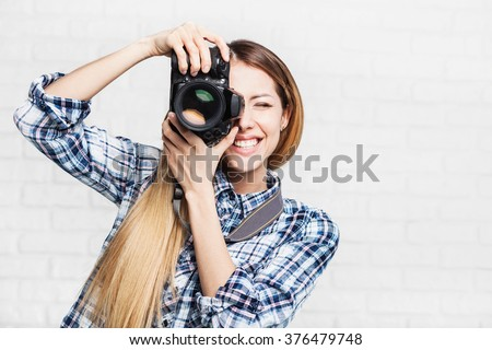 Woman photographer takes images with dslr camera - stock photo