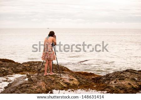 woman photographer takes photo of the beautiful seascape - stock photo