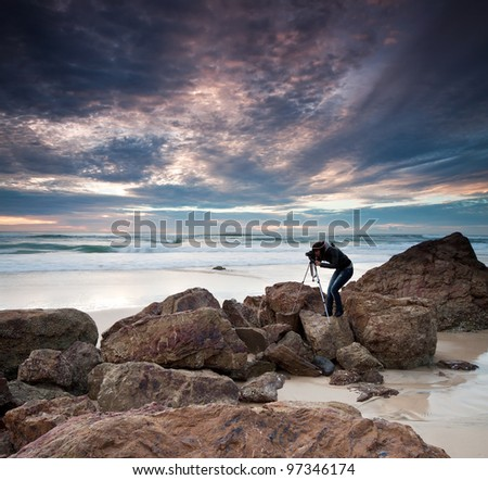 woman photographer takes photo of the beautiful seascape (miami beach, queensland, australia) - stock photo