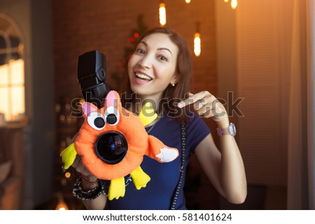 Woman photographer with a children's toy on the camera lens to attract the child's attention