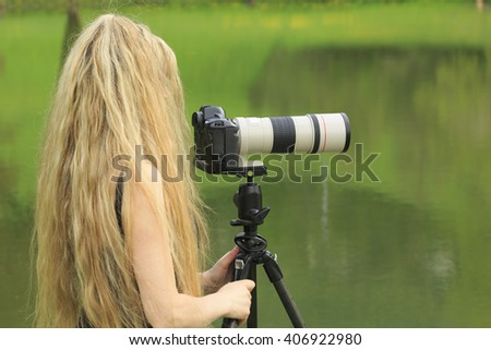Woman photographer with camera outdoors with long blond hair