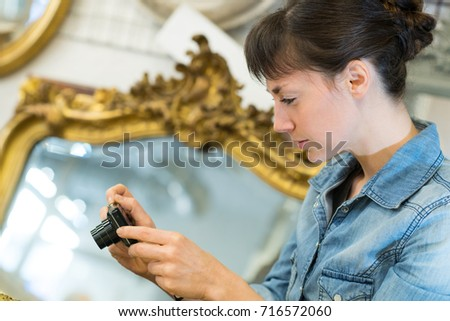 woman photographing antiques