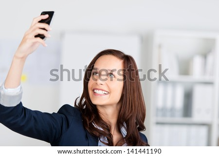 Woman photographing herself with her mobile phone holding it up in the air and smiling - stock photo