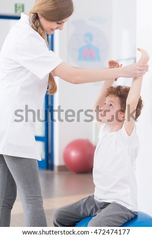 Woman physiotherapist exercising with small ginger boy in light interior