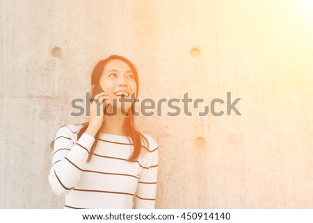 Woman pick up a call with copyspace on wall - stock photo