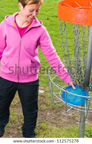 Woman pick up a disc out the basket, vertical format - stock photo