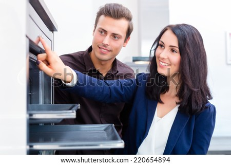 Woman picking oven for domestic kitchen in studio or furniture store showroom - stock photo