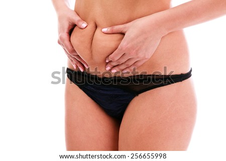 Woman pinches fat on her belly, isolated, white background - stock photo