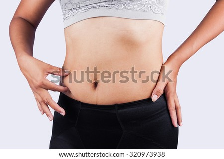 woman pinching belly fat after weight loss,body slim - stock photo