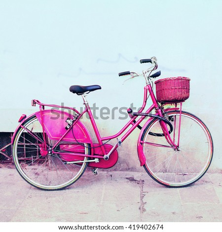 Woman pink bicycle with wicker basket on the old street.