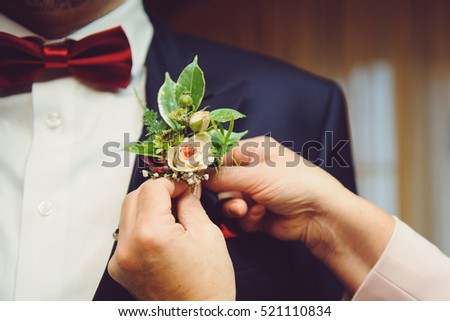 woman pinning boutonniere with lady bird