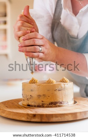 woman piping decoration on a cake - stock photo