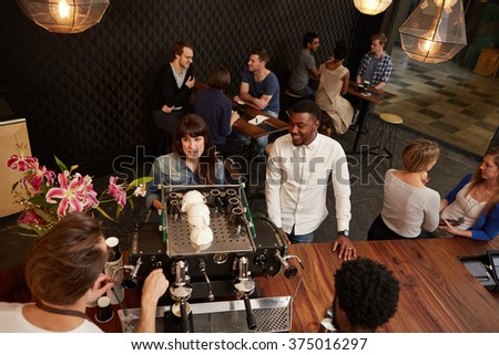Woman placing an order with barista in a modern cafe