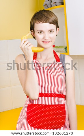 Woman placing order for healthy fresh fruit delivery when talking on a banana telephone in kitchen - stock photo