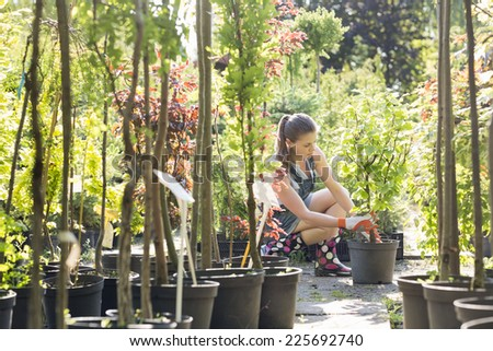 Woman planting pot at garden center - stock photo