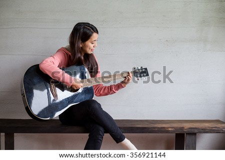 Woman play with guitar at home - stock photo