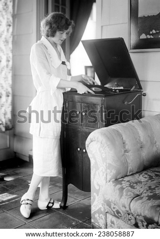Woman playing a record, ca 1930s.