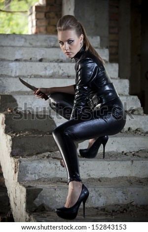 woman playing a spy in leather catsuit, holding a combat knife in fighting pose on stairs