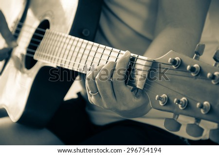 Woman playing acoustic guitar - stock photo