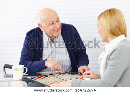 Woman playing backgammon with senior citizen in a retirement home - stock photo
