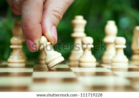 woman playing chess and hold pawn background - stock photo