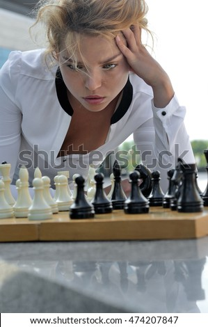 Woman playing chess outdoors. She has long blonde hair and wearing a white shirt