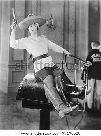 Woman playing cowgirl on mechanical horse - stock photo