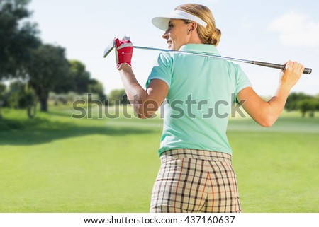Woman playing golf against view of a park