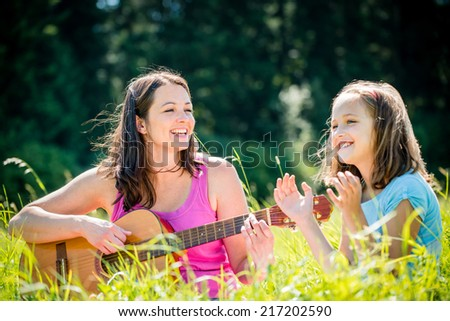 Woman playing guitar to her child outdoor in nature on sunny day